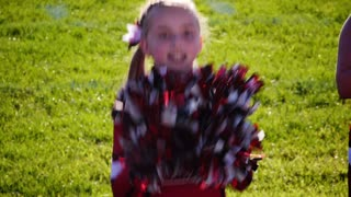 A young girl cheerleader on the sidelines cheers with her pompoms.