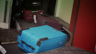 Luggage arrives on a conveyor belt in the baggage claim area of an airport.