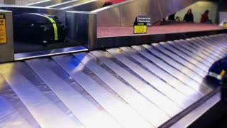 Luggage falls on a moving carousel.