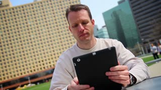 Man Using Tablet PC in an Outdoor Cafe