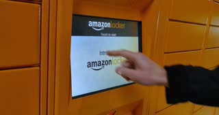 Circa December, 2016 - A man picks up his order from an Amazon Locker station located in a mall. Code on screen has expired and is no longer valid.