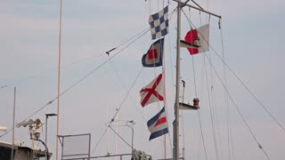 Nautical flags fly over a military ship.