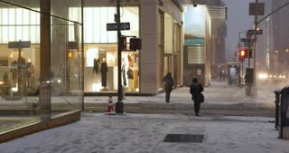 NEW YORK - Circa December, 2016 - A man shovels snow from the sidewalks outside upscale 5th Avenue businesses and storefronts.
