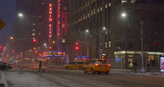 NEW YORK - Circa December, 2016 - A nighttime snowy establishing shot of 6th Avenue in Manhattan with Radio City Music Hall in the distance.