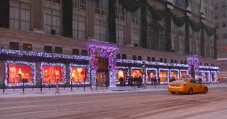 NEW YORK - Circa December, 2016 - A snowy establishing shot of Saks Fifth Avenue's storefront decorated for Christmas and the Holiday season.