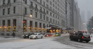 NEW YORK - Circa December, 2016 - A wintry establishing shot of the side entrance of the Plaza Hotel and traffic on Central Park South in Manhattan. DX.