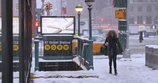 NEW YORK - Circa December, 2016 - A woman, bundled up for the cold, enters a subway station in Manhattan during a blizzard. DX.