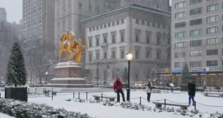 NEW YORK - Circa December, 2016 - Tourists play in the snow near the William Tecumseh Sherman Monument by Central Park.