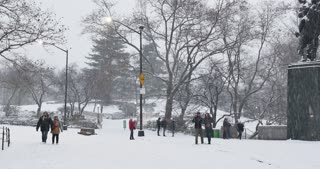 NEW YORK - Circa December, 2016 - Tourists walk and play in the snow near an entrance to Manhattan's Central Park.