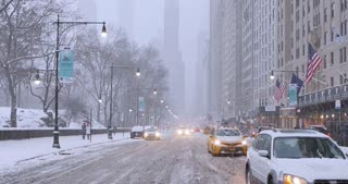 NEW YORK - Circa December, 2016 - Traffic waits at a red light on Central Park South in midtown Manhattan during a snowstorm. DX.