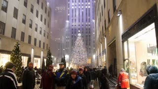 NEW YORK CITY - Circa December, 2013 - Tourists visit the tree outside Rockefeller Center in Manhattan.