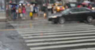 NEW YORK CITY, Circa June, 2015 - Defocused shot of pedestrians with umbrellas dodging raindrops on the streets of New York City.