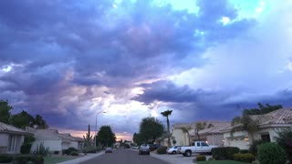 Ominous storm clouds appear over a typical Arizona-style residential neighborhood.