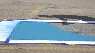 Painting a blue handicapped parking space.