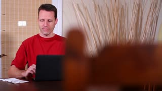 Man at Home at Dining Room Pays Bills on Laptop