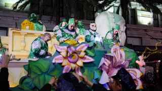 People on a Mardi Gras Float Throw Beads to People Below 4114