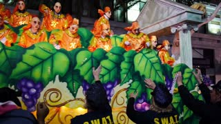 People on a Mardi Gras Float Toss Beads to People Below 4116