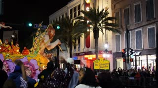 People on a Mardi Gras Float Toss Beads to People Below 4120