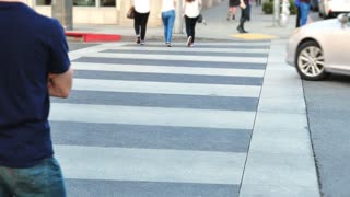 People walking in a crosswalk on Rodeo Drive in Beverly Hills.