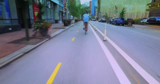 PITTSBURGH - Circa July, 2016 - Following a biker in the bicycle lane on Penn Avenue past the bars, restaurants, and hotels in downtown Pittsburgh.