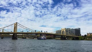 PITTSBURGH, PA - Circa September, 2015 - The Gateway Clipper Tour Boat carries passengers and tourists on the Allegheny River in Pittsburgh as a speed boat passes by.
