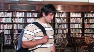 Proud Student in Library Smiles at Camera