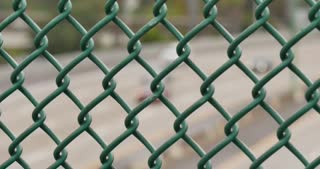 SAN DIEGO, CA - Circa February, 2017 - A closeup slowly moving dolly shot of traffic passing on I-5 in San Diego as seen through a wire fence.