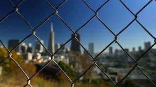 SAN FRANCISCO, CA - Circa October,  2015 - An establishing shot of the San Francisco  skyline as seen through a chain link fence.