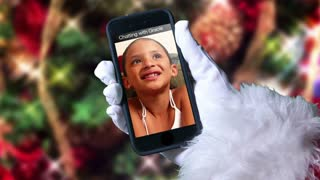 Santa Claus video chats with a young girl on his smartphone. With optional luma matte for custom background usage.