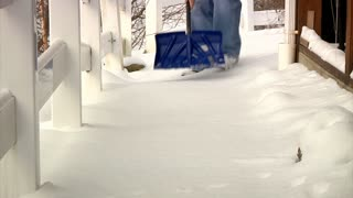 Man Shovel Snow off Sidewalk