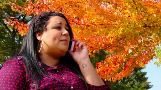Young Mixed Race Woman Talking on a Cell Phone Outside