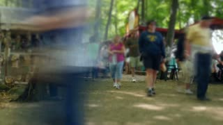 Timelapse, blurred motion of a large crowd at a fair in the woods.