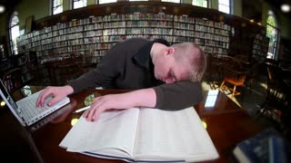 Tired Student in College Library Studying