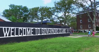 Tourists and visitors walk past the welcome sign on their visit to Governors Island, New York.