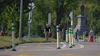 Two college-aged guys ride their bicycles in a bike lane in Schenley Park in the Oakland area of Pittsburgh, PA.  Shot at 60fps.