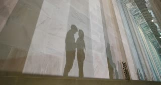 Two lovers kiss at the base of the Lincoln Memorial at night while their shadows fall on the marble walls.