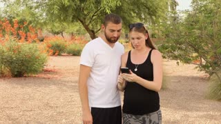 Two millennials play an augment reality game on a smartphone in a typical Arizona public park.