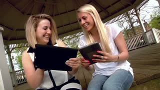 Two Women Use iPads in the Park