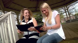 Two Women Use Tablet PCs in the Park
