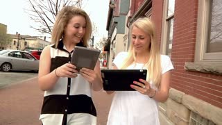 Two Women Walk in Town with Tablet PCs