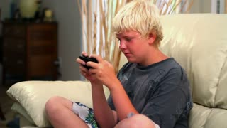 Young Boy Plays Videogame on Sofa