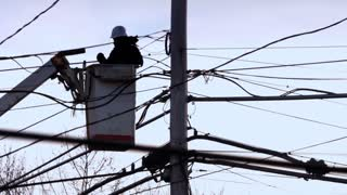 A back-lit silhouetted electrical utility worker in a bucket truck examines a telephone pole.