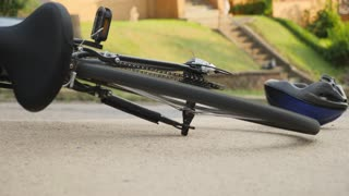 A bicycle lays on the sidewalk with the wheels spinning after an accident as traffic passes by.