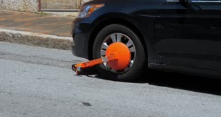 A bright orange boot is placed on a parked car in a city.