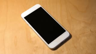 A cellular telephone on a desk rings with a phone call from Russia. The call is declined. Phone number and screen are fictional.