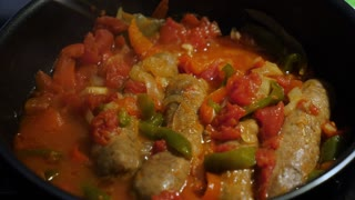 A close up shot of cooking sausages or bratwurst links and vegetables in a pan on a stovetop.
