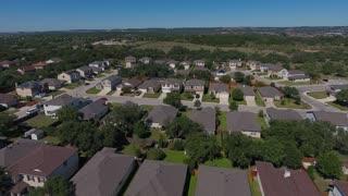 A daytime aerial establishing shot of a typical San Antonio, Texas residential neighborhood.