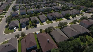 A daytime aerial establishing shot of a typical San Antonio, Texas residential neighborhood.