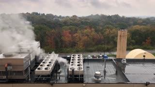 A daytime autumn establishing shot of an industrial building's rooftop.