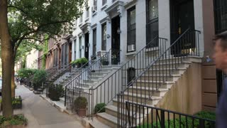 A daytime establishing shot (DX) of typical upscale row houses or brownstones lining a residential street in Manhattan or Brooklyn.